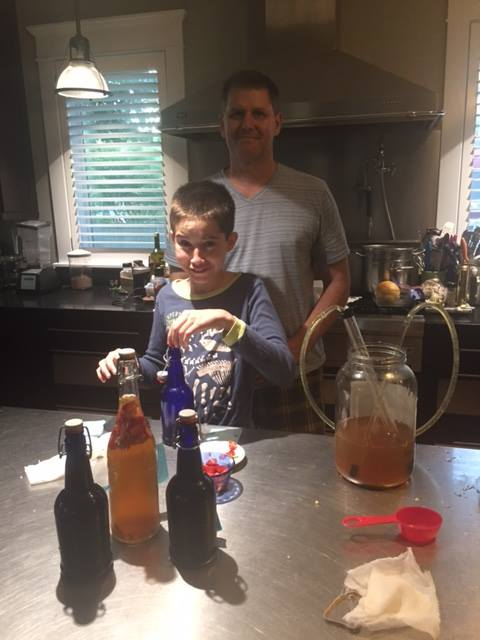 A Steinbartonian and his son bottling kombucha in their kitchen.