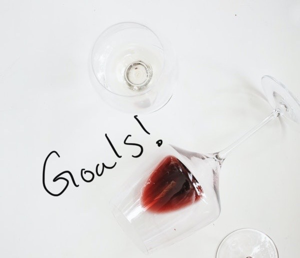 "Three wine glasses on a stark white backround. The middle is on its side and has red wine gently lying in the bowl of the glass. It is not spilled. The image says ""Goals!"" in handwriting."