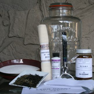 Kombucha kit containing a fermentor, scoby, cheesecloth, tea, sugar, steeping bag, stick-on thermometer, sanitizer, and instructions.