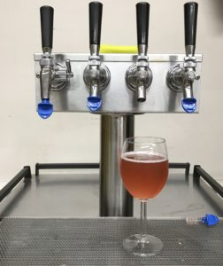 Rosè wine in a wine glass under a tap system to illustrate kegged wine or draft wine.