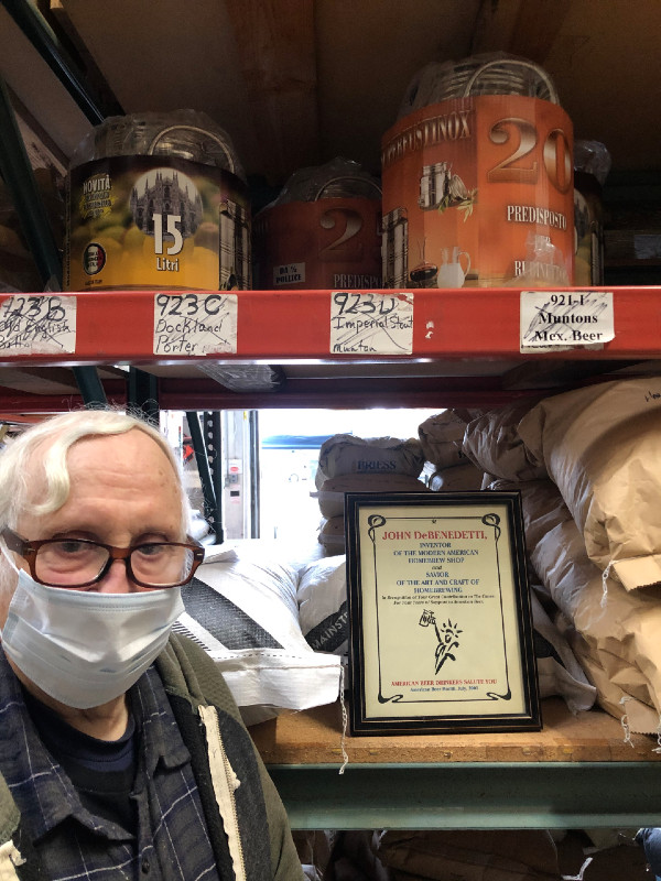 "FHS owner John DeBenetti standing in front of grain bags in his warehouse with a certificate from 2001 thanking him for ""founding the modern American homebrew shop"" and ""savior of the art and craft of homebrewing."""
